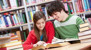 Portrait of teenage girl reading book with her classmate near by
